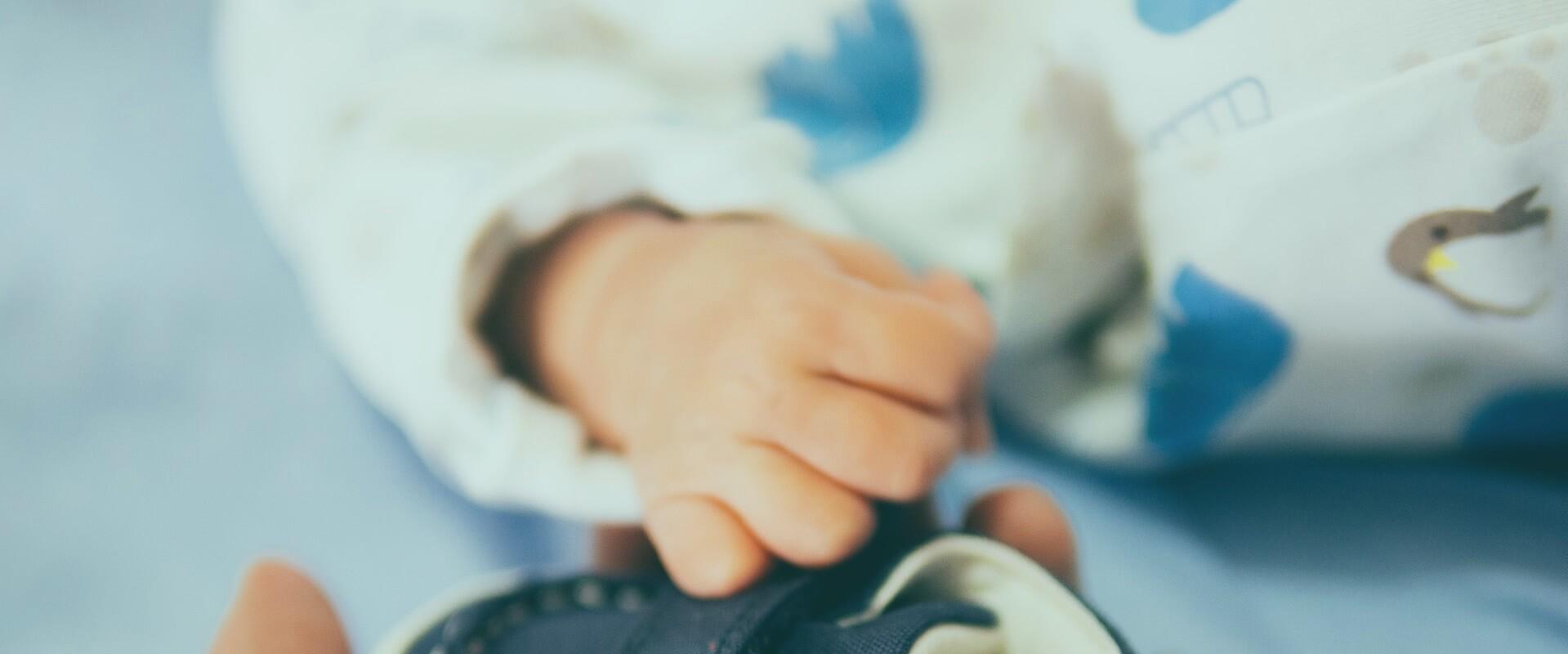 Een babyhandje dat een kinderschoentje vasthoudt